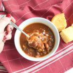 instant pot venison chili on red napkin with corn bread and hand with spoon