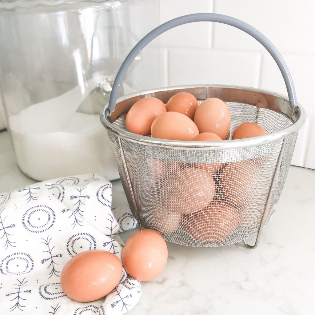 brown eggs in Instant Pot Steamer basket with tea towel on white counter