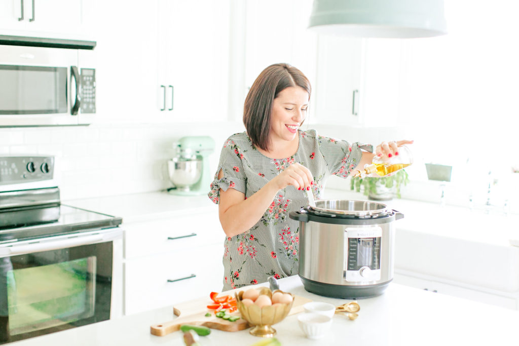 woman cooking with ultra instant pot in white kitchen