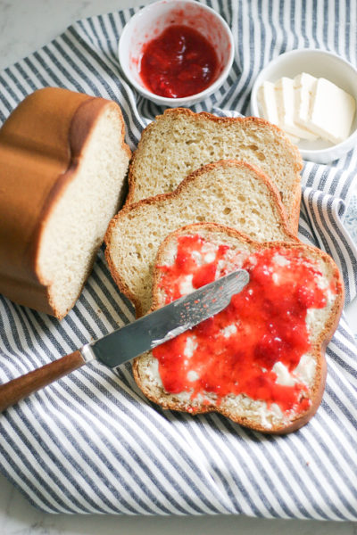 Bread machine gluten free bread with butter and jam with a knife