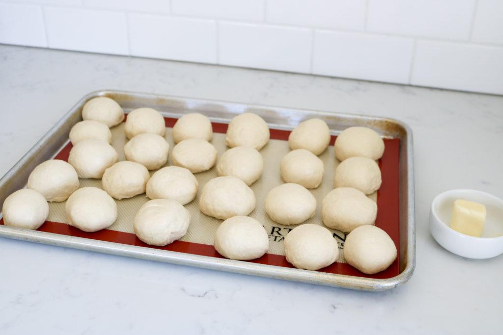 dinner roll dough balls on a cookie sheet