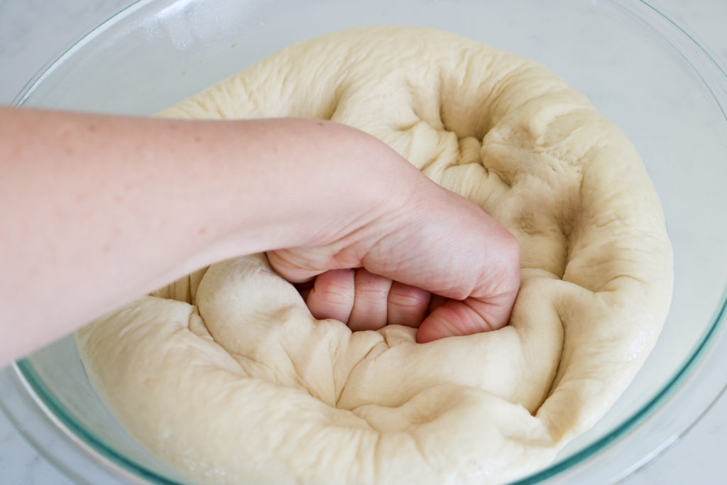 fist punching down homemade bread dough