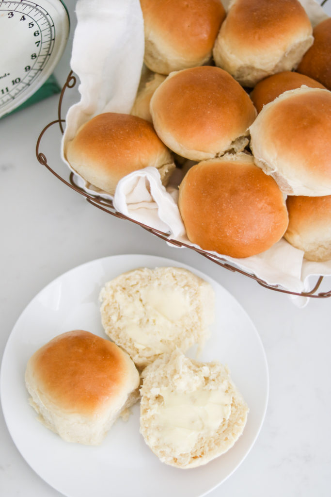 homemade rolls in a wire basket with some butter on top