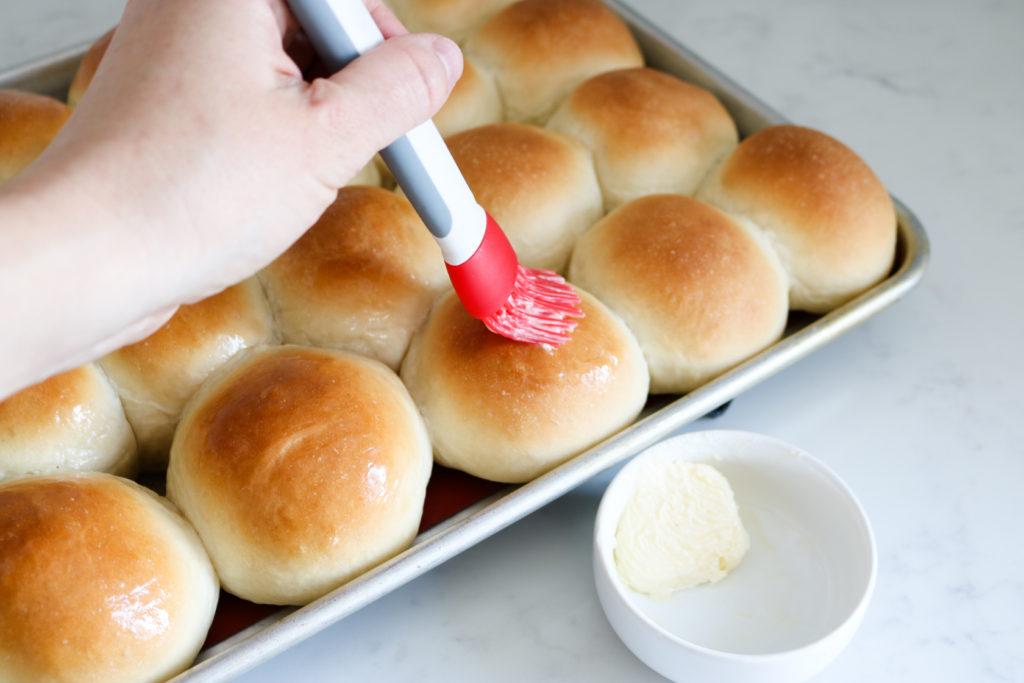basting butter on fresh homemade dinner rolls