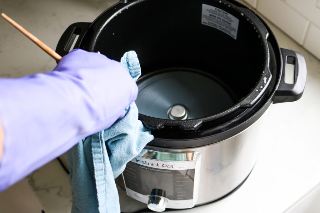 gloved hand cleaning the instant pot rim