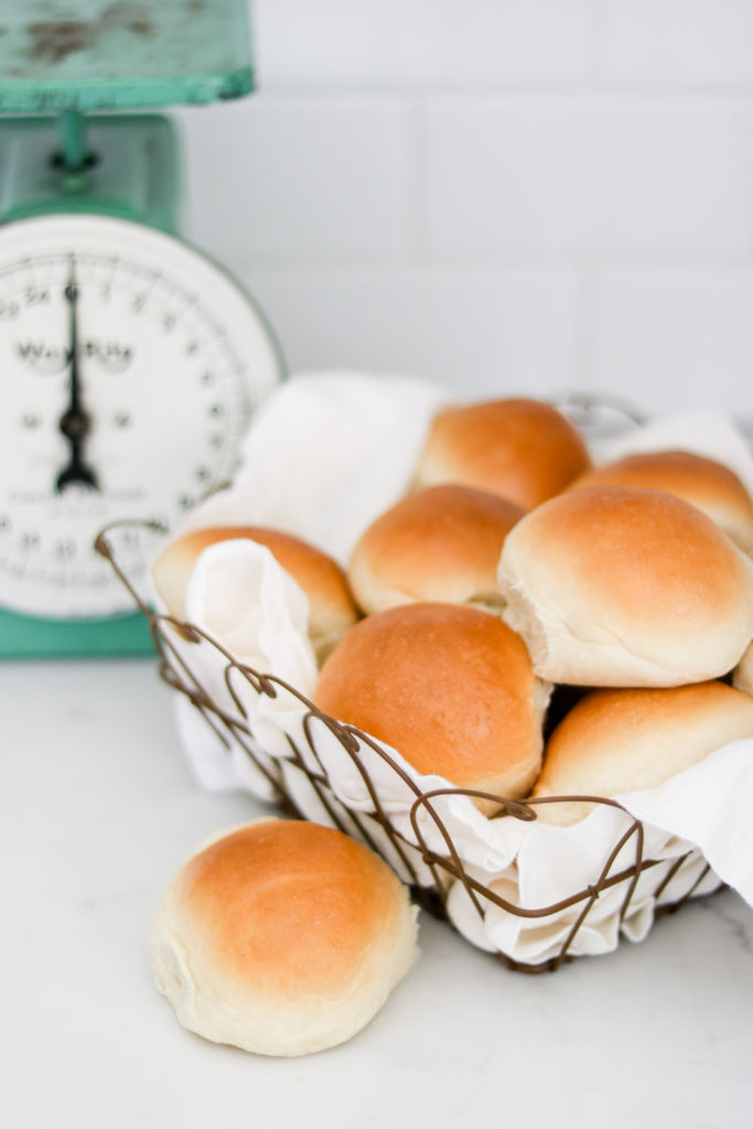 homemade rolls in a wire basket with vintage scale in the background