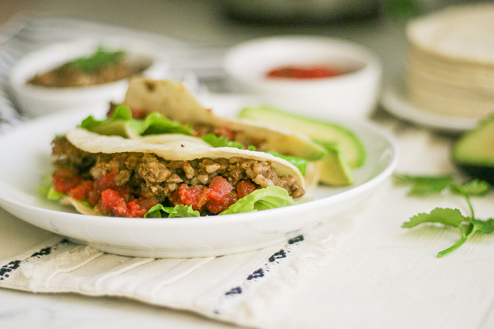Instant Pot Mexican Lentil Tacos on a white plate with salsa in background