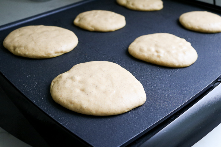 Gluten free pumpkin pancakes cooking on electric griddle