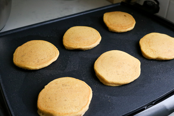 Gold brown cooked gluten free pumpkin pancakes on electric griddle