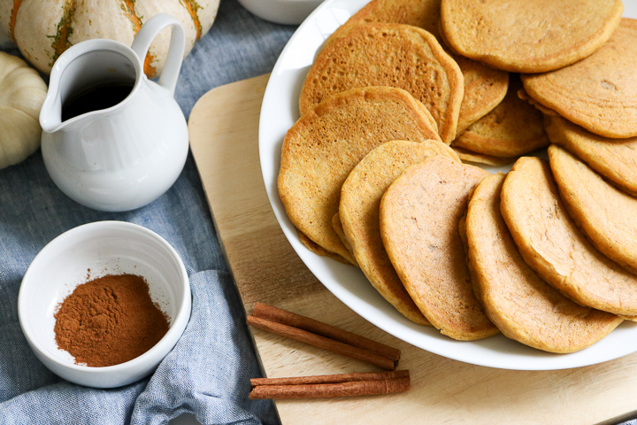 Freshly cooked gluten free pumpkin pancakes on a white plate