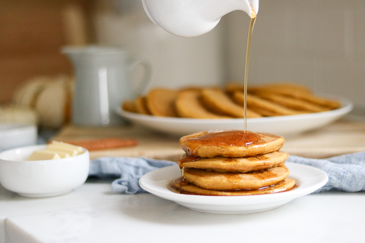 Maple syrup pouring onto gluten free pumpkin pancakes