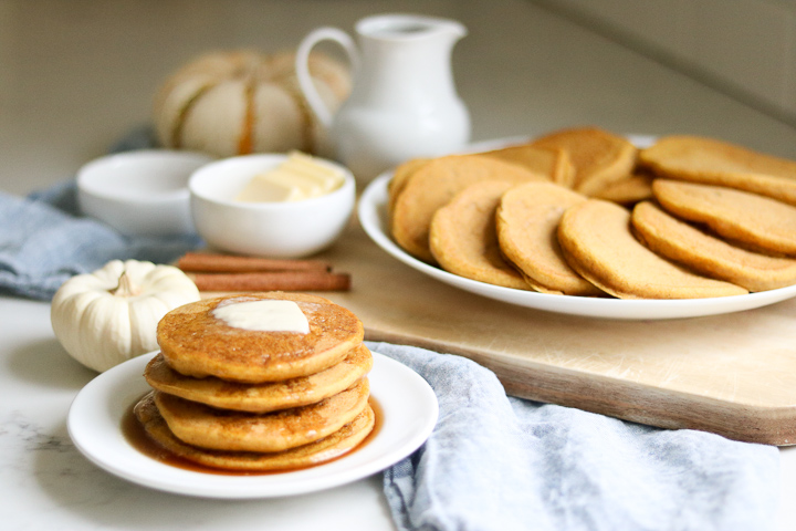 Gluten free pumpkin pancakes with syrup in the background