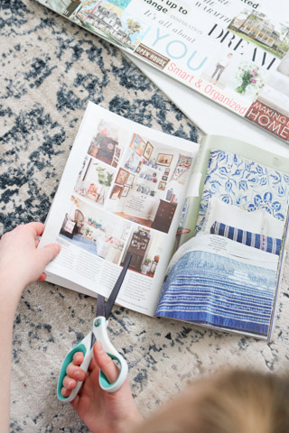 Scissors cutting out vision board inspiration from magazines