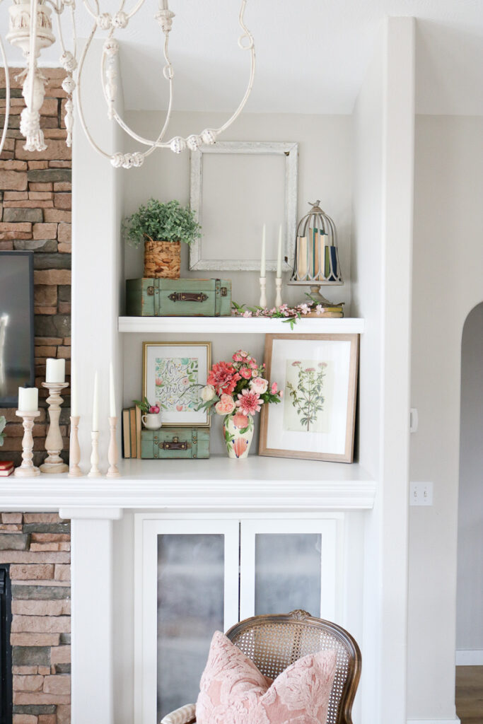 Pink floral bouquet with frames on shelves