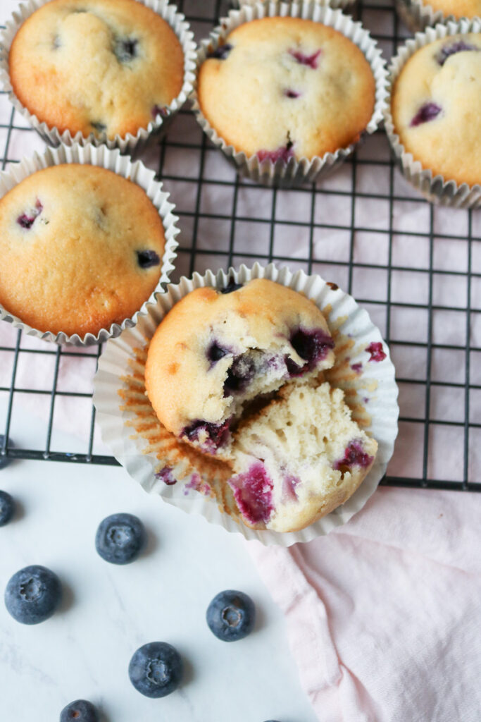 blueberry muffin with a bite taken on a cooling rack