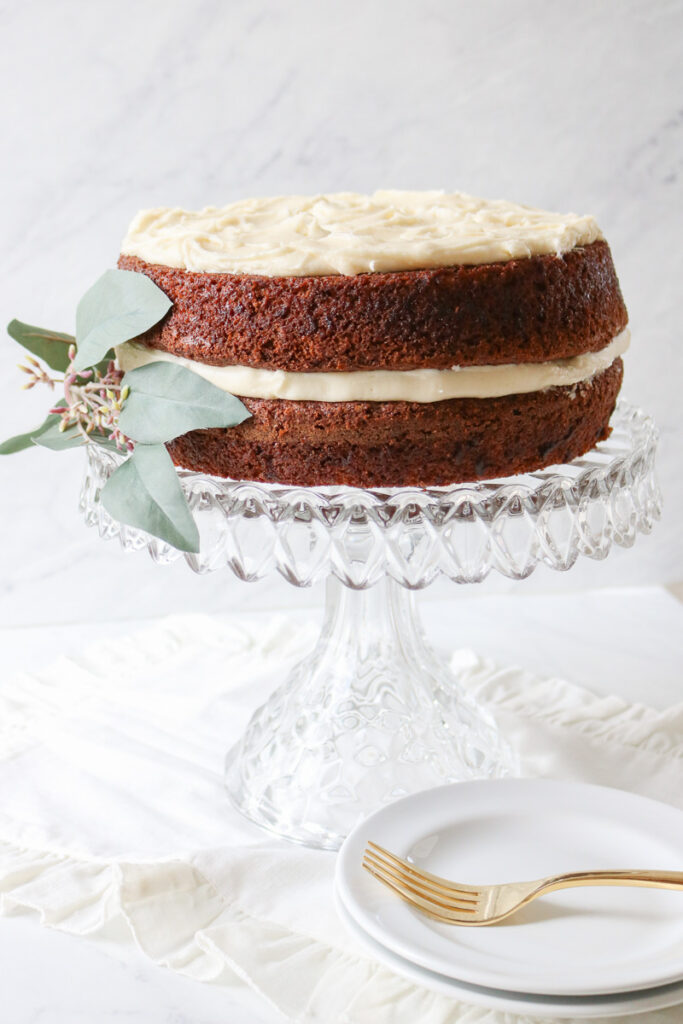 layered carrot cake with cream cheese frosting with green leaf decoration on a glass cake pedestal