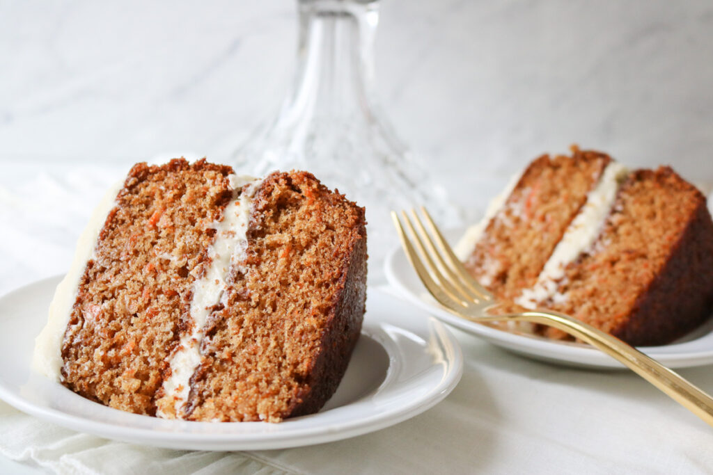 2 slices of carrot cake on white plates with gold fork