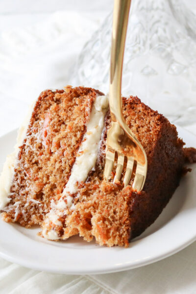 fork taking a bite of carrot cake slice