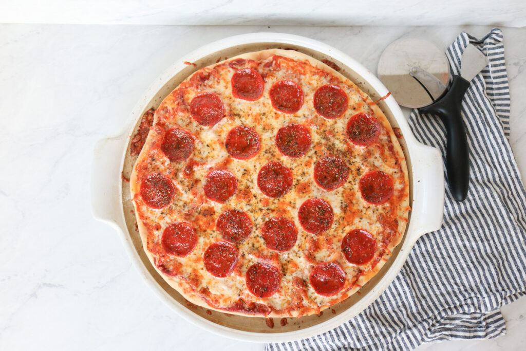 Large pepperoni pizza on pizza pan