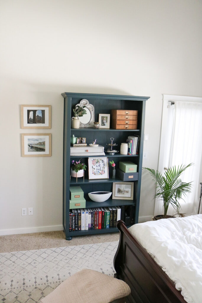 blue green grey bookshelf with plant to the right and frames on the wall to the left