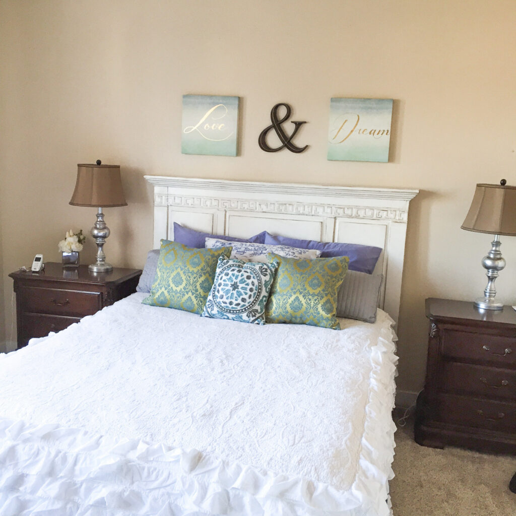 white bed with white quilt, nightstands and wall art