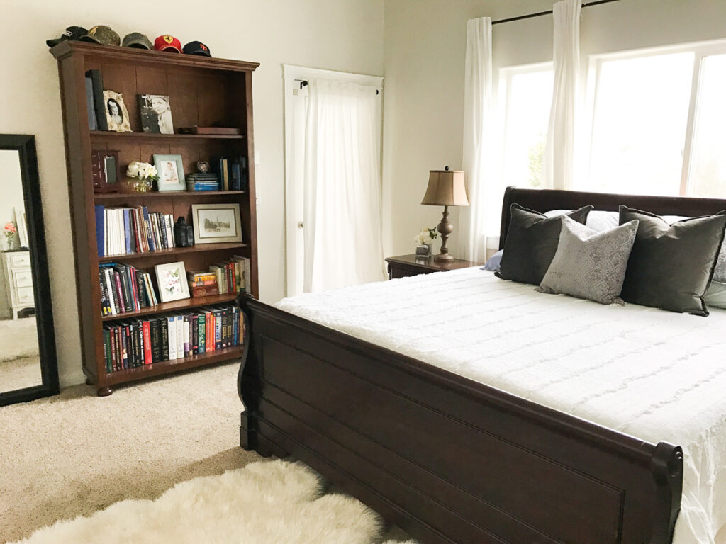 sleigh bed with white bedding in front of a window with a bookshelf to the left