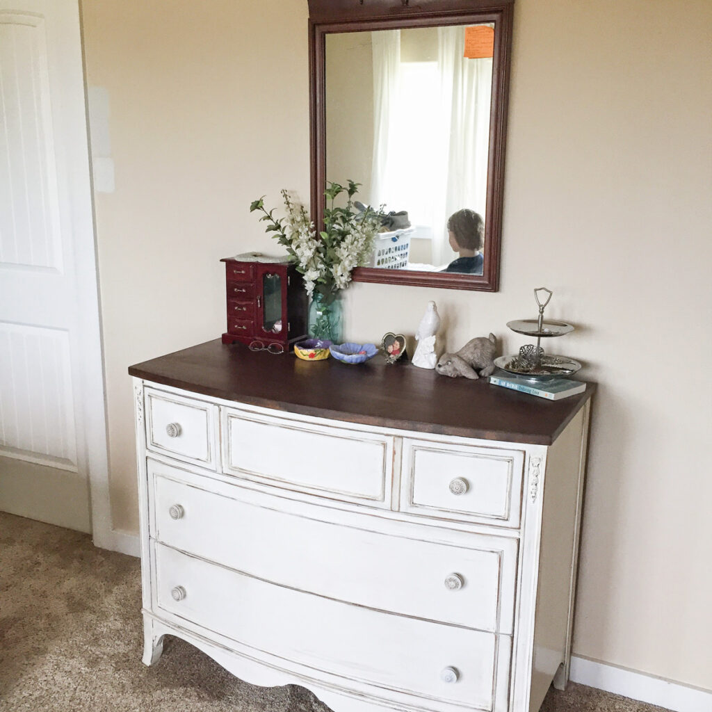 white dresser with jewelry box, flowers on top and mirror on wall