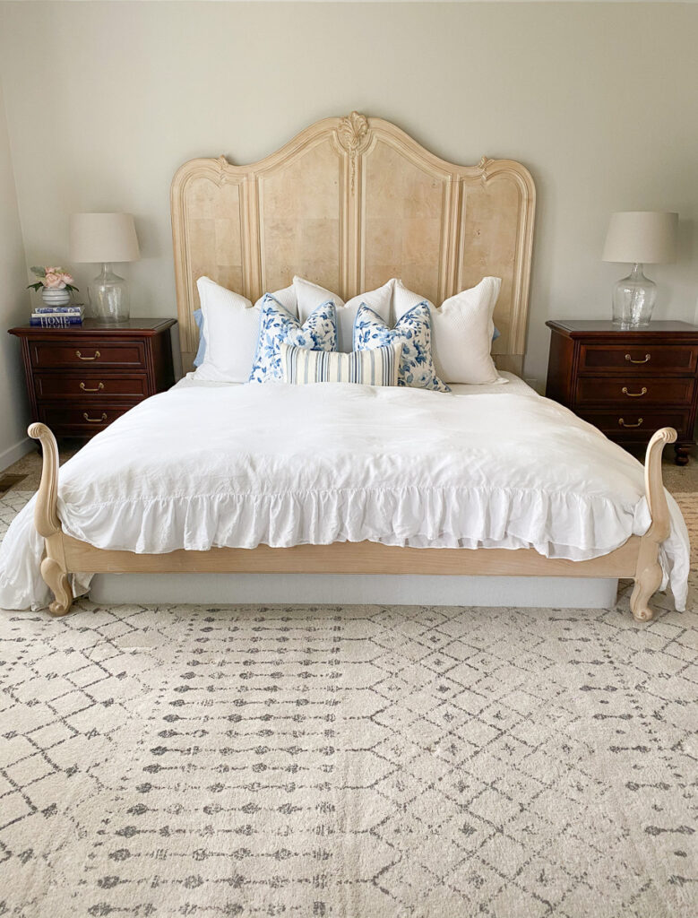 french country style king bed with white ruffle duvet and nightstands