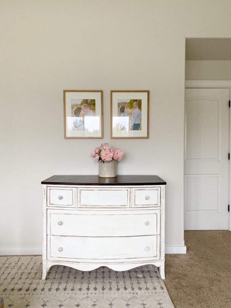 white dresser with flowers in a pot on top and frames on wall