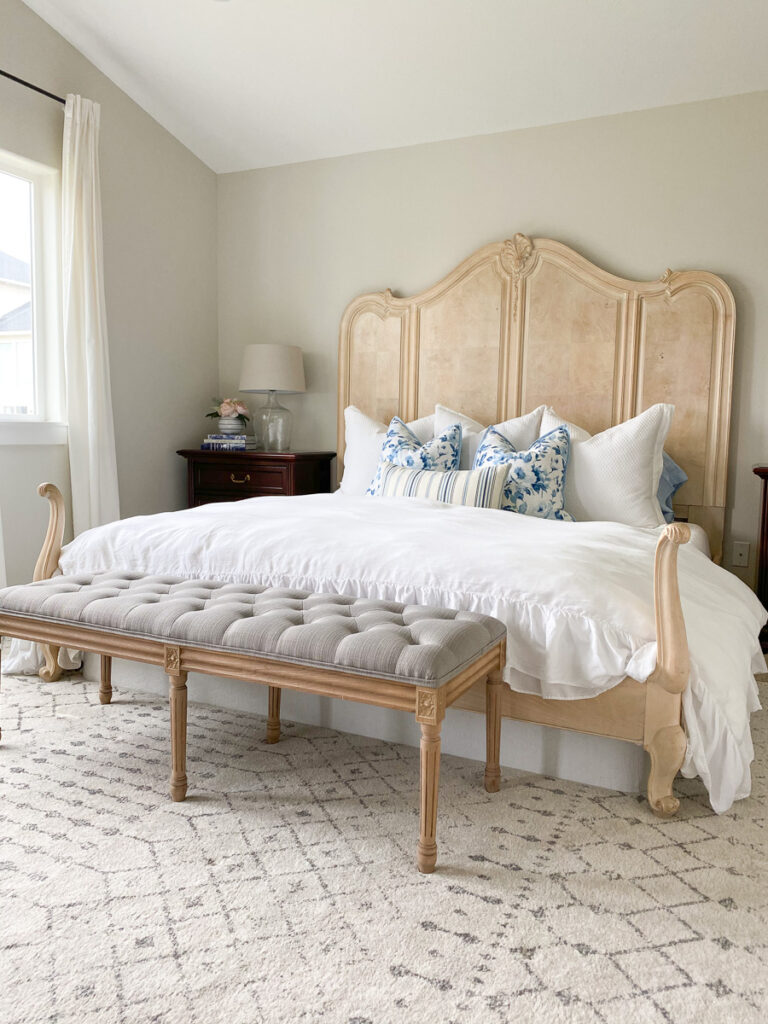 french country style king bed with white ruffle duvet and bench
