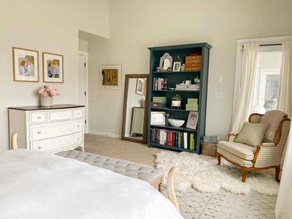 master bedroom with green painted bookshelf, rug, chair and dresser