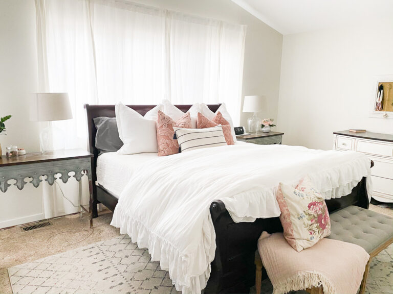 Sleigh bed in front of windows with throw pillows and white bedding