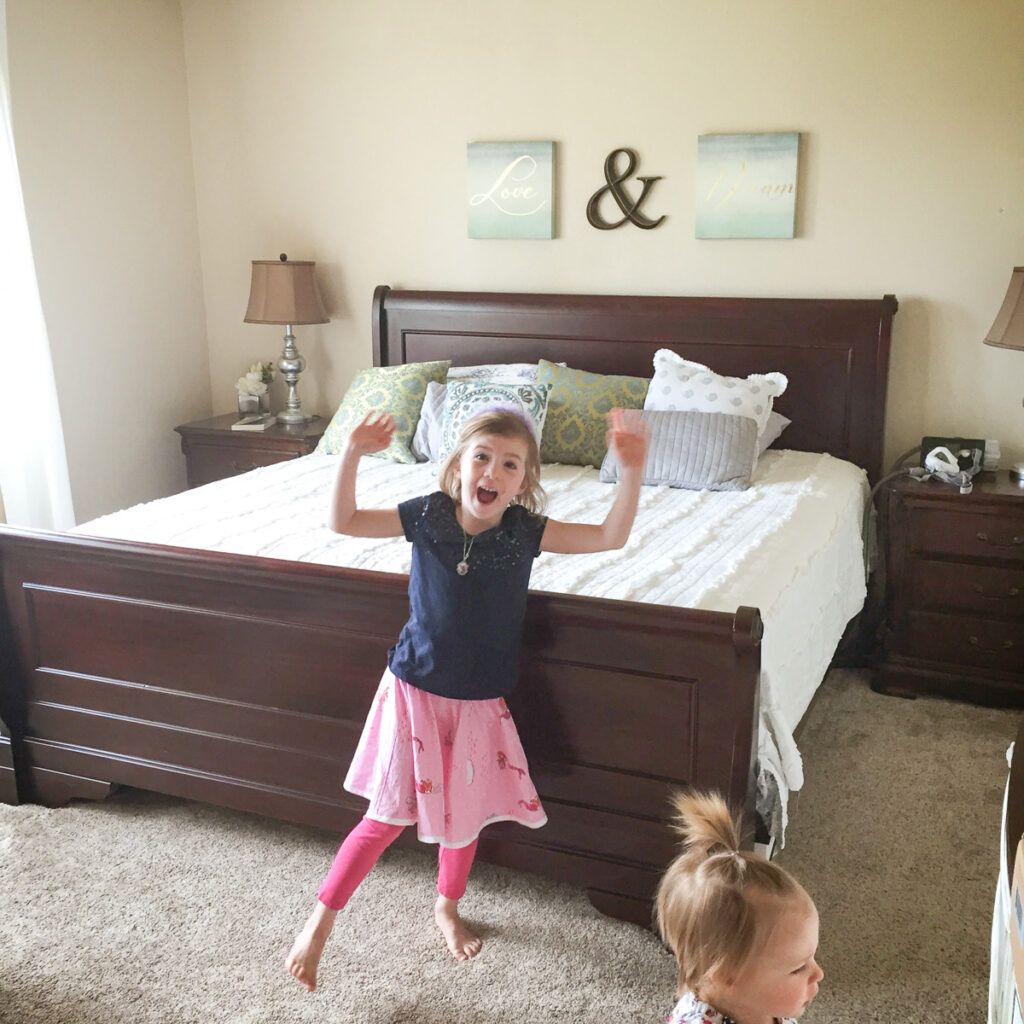 kids in front of sleigh bed with white bedding
