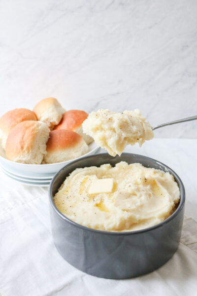 mashed potatoes on a spoon with a bowlful below and bread rolls in background
