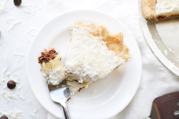 cream pie with a fork bite on white plate