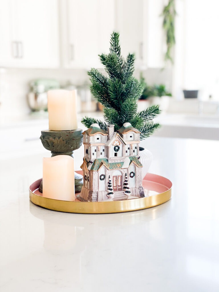 miniature house with candles and christmas tree on kitchen island