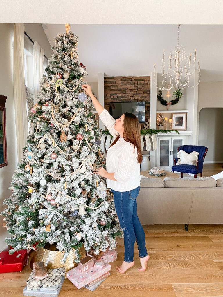 woman putting christmas ornaments on tree
