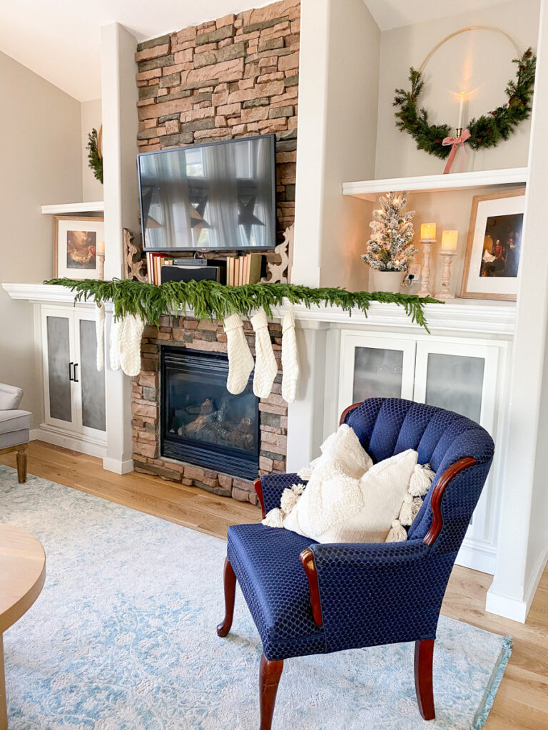 christmas decor on builtin shelving, stockings and accent chair