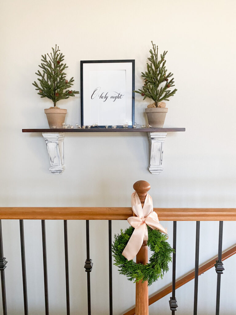 christmas word art in frame on shelf with two christmas trees