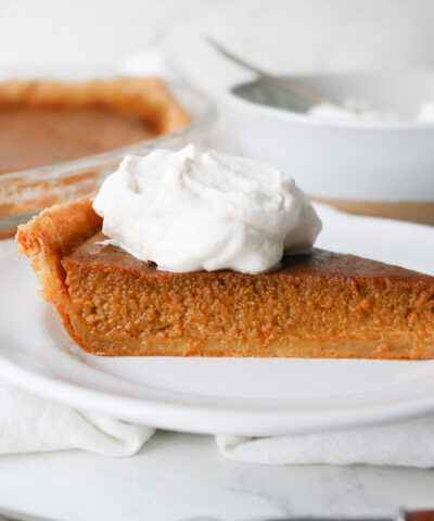 slice of pumpkin pie with whipped cream on top on a white plate